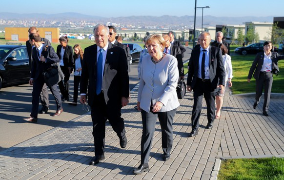 epa05427220 German Chancellor Angela Merkel (C-R) speaks to President of Switzerland Johann Schneider-Ammann (C-L) at the ASEM Village on the sidelines of the the 11th Asia-Europe Meeting (ASEM) Summit of Heads of State and Government (ASEM11) in Ulan Bator, Mongolia, 16 July 2016. Mongolia hosts the 11th ASEM Summit of Heads of State and Government (ASEM11) in its capital city Ulan Bator from 15 to 16 July 2016.  EPA/KAY NIETFELD