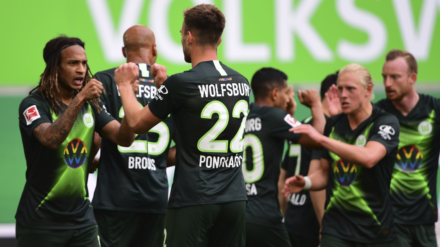 Wolfsburg's Kevin Mbabu, center, celebrates with team mate after scoring during the German Bundesliga soccer match between VfL Wolfsburg and Eintracht Frankfurt in Wolfsburg, Germany, Saturday, May 30, 2020. Because of the coronavirus outbreak all soccer matches of the German Bundesliga take place without spectators. (Swen Pfoertner/Pool via AP)