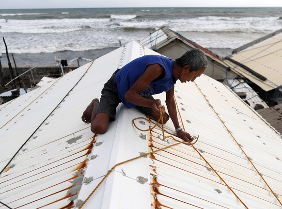 epaselect epa07018664 A Filipino villager secures the roof of a house in the town of Aparri, Cagayan province, Philippines, 14 September 2018. Typhoon Mangkhut, ranked as the most powerful of the year to enter the Philippines braces for the arrival of the storm that is expected to hit the northern island of Luzon. The category 5 typhoon, Mangkhut, named Ompong in the Philippines, is moving with sustained winds of 205 kph (127 mph) and gusts of 255 kph off the eastern coast of Luzon, according to the Philippine meteorological service Philippine Atmospheric, Geophysical and Astronomical Services Administration (PAGASA).  EPA/FRANCIS R. MALASIG