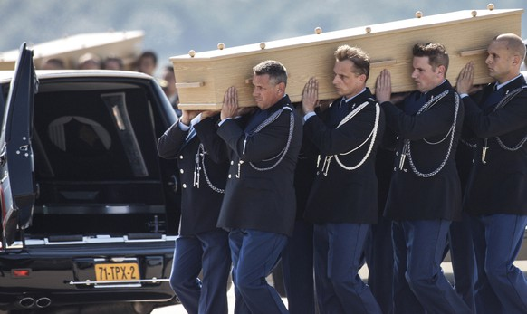 Coffins of the victims of Malaysia Airlines MH17 downed over rebel-held territory in eastern Ukraine, are loaded into hearses on the tarmac during a national reception ceremony at Eindhoven airport July 23, 2014. Two aircraft carrying the remains of some of the 298 passengers who died on flight MH17 touched down at an airport in the Dutch city of Eindhoven on Wednesday, as next-of-kin and Dutch and foreign officials looked on. The remains of the victims of the downing of the flight over eastern Ukraine, 193 of whom were Dutch, will be brought over the next few days to a military base in Hilversum, the Netherlands. The Netherlands declared Wednesday the country's first day of mourning in more than half a century.      REUTERS/Mischa Rapmund  (NETHERLANDS - Tags: TRANSPORT POLITICS DISASTER CIVIL UNREST)