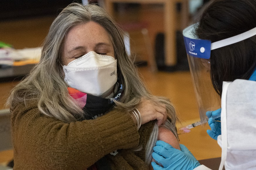 Teacher Lisa Egan is vaccinated with the Moderna coronavirus vaccine at a clinic organized by New York City's Department of Health, Monday, Jan. 11, 2021.