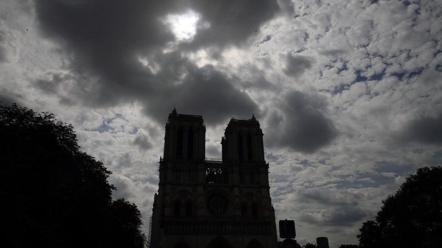 Notre Dame cathedral is silhouetted as environmental groups and unionists attend a news conference to warn against lead particles polluting the air in the area, and ask for a regularly updated chart showing pollution levels in Paris, France, Monday, Aug. 5, 2019. Hundreds of tons of toxic lead in Notre Dame's spire and roof melted during the April fire. (AP Photo/Francois Mori)