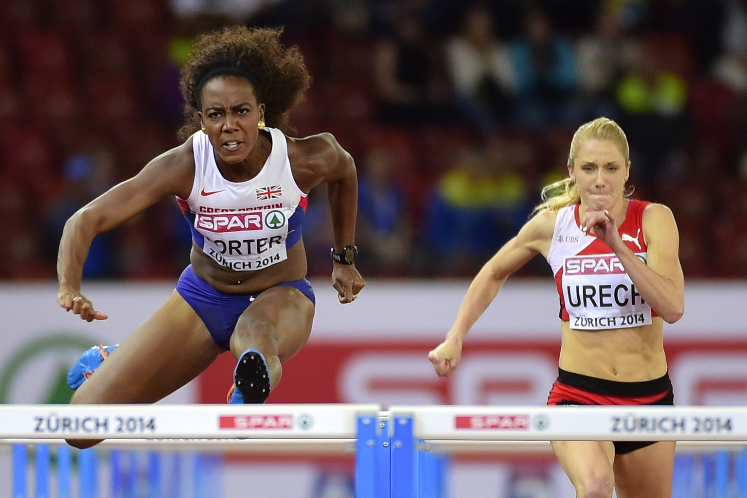 Great Britain's Tiffany Porter (L) and Switzerland's Lisa Urech compete in the Women's 100m hurdles semi-final during the European Athletics Championships at the Letzigrund stadium in Zurich on August 12, 2014.  AFP PHOTO / OLIVIER MORIN