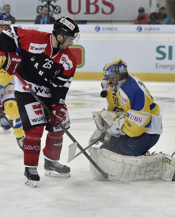 epa04540732 Davos' goalkeeper Leonardo Genoni (R) fights for the puck against Team Canada's Mike Hedden (L), during the game between Switzerland's HC Davos and Team Canada at the 88th Spengler Cup ice hockey tournament in Davos, Switzerland, 26 December 2014.  EPA/PETER SCHNEIDER