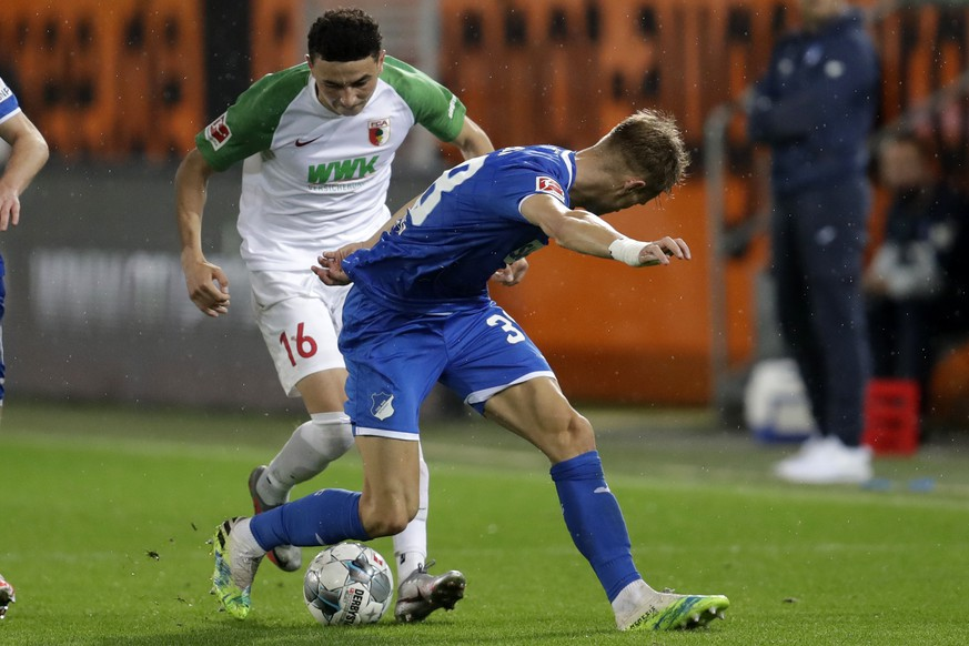 Augsburg's Ruben Vargas, left, controls the ball as Hoffenheim's Stefan Posch defends during the German Bundesliga soccer match FC Augsburg against TSG 1899 Hoffenheim in Augsburg, Germany, Wednesday, June 17, 2020. (AP Photo/Michael Probst, Pool)