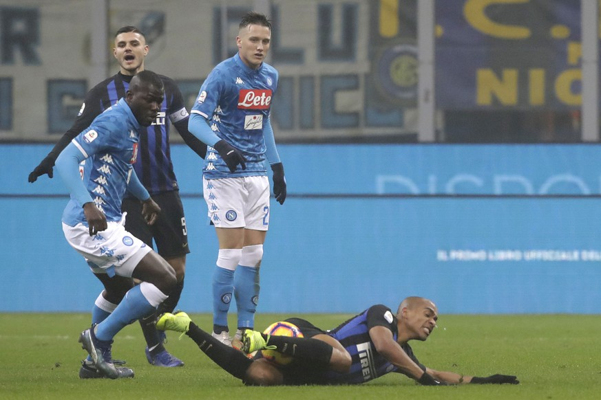 Inter Milan's Joao Mario, right, is fouled by Napoli's Kalidou Koulibaly during a Serie A soccer match between Inter Milan and Napoli, at the San Siro stadium in Milan, Italy, Wednesday, Dec. 26, 2018. (AP Photo/Luca Bruno)
