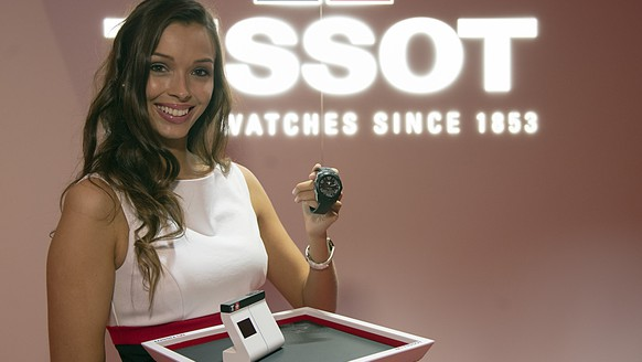 A hostess shows a connected watch at the booth of Tissot at the official opening day of the world watch and jewellery show