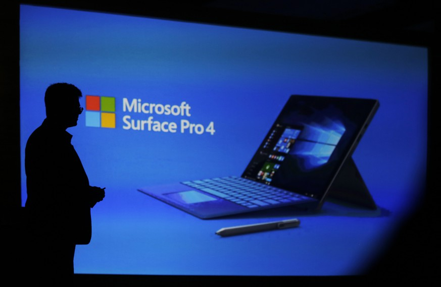 Microsoft Windows Business Group's India director, Vineet Durani, is silhouetted against a screen during the launch of Microsoft Surface Pro4 laptop cum tablet in New Delhi, India, Thursday, Jan. 7, 2016. (AP Photo/Altaf Qadri)