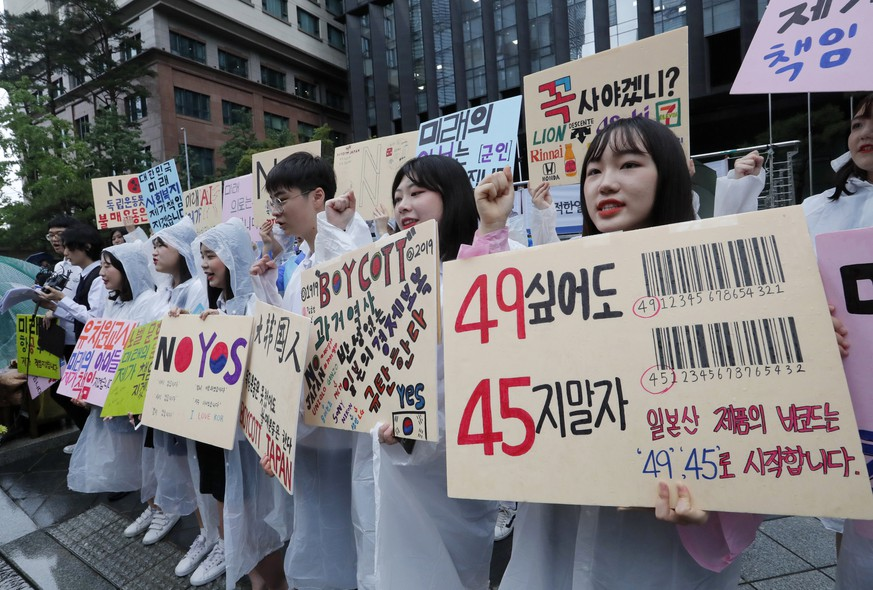 South Korean high school students shout slangs during a rally denouncing the Japanese government's decision on their exports to South Korea in front of the Japanese embassy in Seoul, South Korea, Friday, July 26, 2019. The signs read: