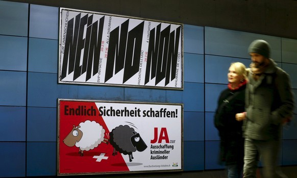 A poster of Swiss People's Party (SVP), demanding to vote for an initiative to deport criminal foreigners, is placed underneath another one against it at the central railway station in Zurich, Switzerland in this February 12, 2016 file photo. Swiss voters will face decisions on whether to deport foreign lawbreakers to building a second tunnel through the Gotthard mountain range when they go to the polls on Sunday.   The poster on top reads,