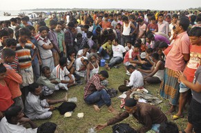 Relatives wait for news of the passengers after the M.V. Miraj-4 ferry capsized, by the Meghna river at Rasulpur in Munshiganj district May 15, 2014. The Bangladeshi river ferry with around 200 passengers on board capsized in a storm on Thursday, killing at least 12 people, and a rescue diver said he had seen more bodies inside the wreck.     REUTERS/Stringer (BANGLADESH - Tags: DISASTER MARITIME)