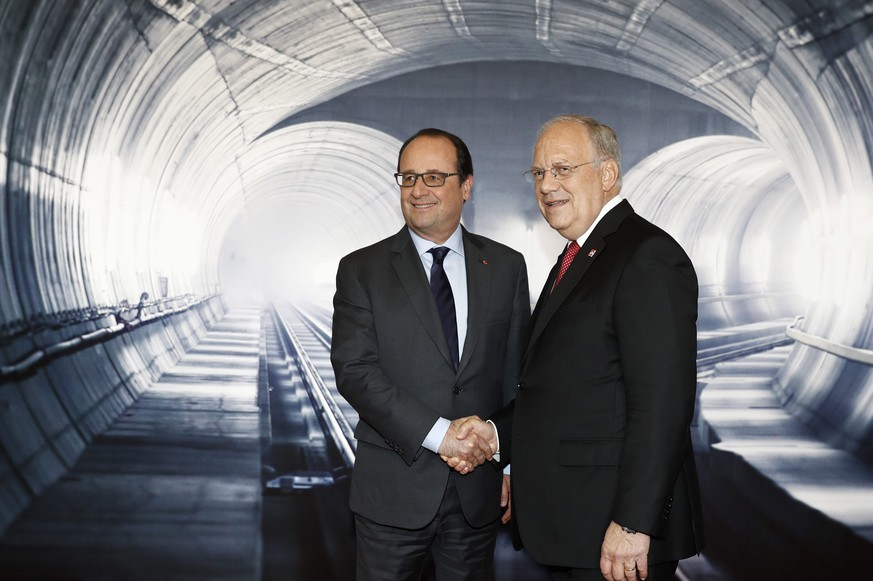 epa05339961 Swiss Federal President Johann Schneider-Ammann (R) welcomes French President Francois Hollande (L) on the opening day of the Gotthard rail tunnel, the longest tunnel in the world, at the fairground Rynaecht at the northern portal in Erstfeld, Switzerland, 01 June 2016. The construction of the 57 kilometer long tunnel began in 1999, the breakthrough was in 2010. After the official opening on 01 June, the commercial opperation will commence on December 2016.  EPA/PETER KLAUNZER / POOL