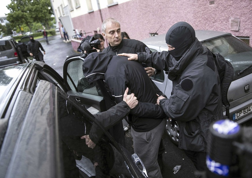 French police officers detain a suspect during a raid in a Strasbourg suburb, eastern France, Tuesday May 13, 2014. The interior minister says police have arrested six people in northeastern France in a roundup of suspected jihadists who travelled to fight in Syria's civil war. The sweep around dawn Tuesday in Strasbourg comes weeks after authorities announced a new push to stop French militants from travelling to Syria. (AP Photo/Jean Francois Badias)