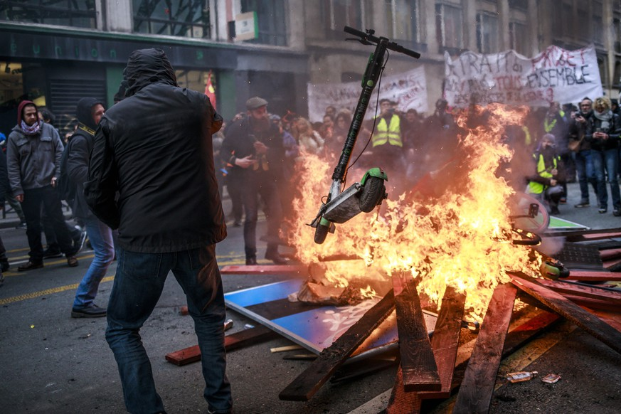 epa08092889 Protesters and 'Gilets Jaunes' (Yellow Vests) throw scooters into a burning fire barricade during a demonstration against pension reforms lead by French Unions in Paris, France, 28 December 2019. Unions representing railway and transport workers and many others in the public sector have called for a 24th days consecutive general strike and demonstration to protest against French government's reform of the pension system.  EPA/CHRISTOPHE PETIT TESSON