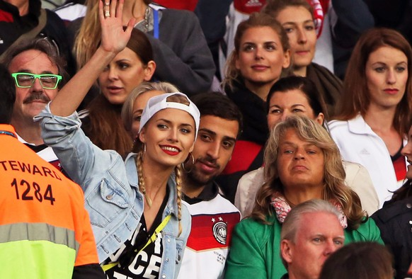 epa04292528 Germany's Sami Khedira's girlfriend Lena Gercke, his brother Denny Khedira, and his mother Doris cheer on the stands during the FIFA World Cup 2014 round of 16 match between Germany and Algeria at the Estadio Beira-Rio in Porto Alegre, Brazil, 30 June 2014.   (RESTRICTIONS APPLY: Editorial Use Only, not used in association with any commercial entity - Images must not be used in any form of alert service or push service of any kind including via mobile alert services, downloads to mobile devices or MMS messaging - Images must appear as still images and must not emulate match action video footage - No alteration is made to, and no text or image is superimposed over, any published image which: (a) intentionally obscures or removes a sponsor identification image; or (b) adds or overlays the commercial identification of any third party which is not officially associated with the FIFA World Cup)  EPA/OLIVER WEIKEN   EDITORIAL USE ONLY