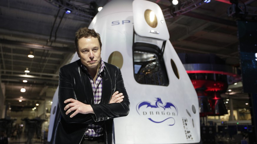 FILE - In this Thursday, May 29, 2014 file photo, Elon Musk, CEO and CTO of SpaceX, listens to a question during a news conference in front of the SpaceX Dragon V2 spacecraft, designed to ferry astronauts to low-Earth orbit, at the headquarters in Hawthorne, Calif. The capsule was named for