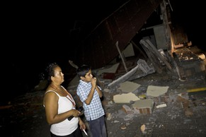 A woman and boy stand near a home that was damaged by an earthquake in Nagarote, Nicaragua, Thursday, April 10, 2014. A 6.1-magnitude earthquake damaged dozens of houses in western Nicaragua on Thursday, and authorities said some people were injured by falling ceilings, beams and walls. (AP Photo/Esteban Felix)