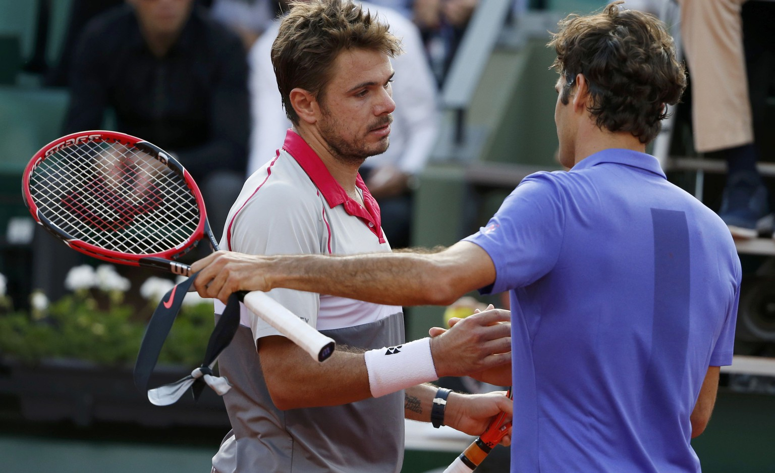 Stan Wawrinka of Switzerland shakes hands with his compatriot Roger Federer after winning their men's quarter-final match during the French Open tennis tournament at the Roland Garros stadium in Paris, France, June 2, 2015.           REUTERS/Vincent Kessler