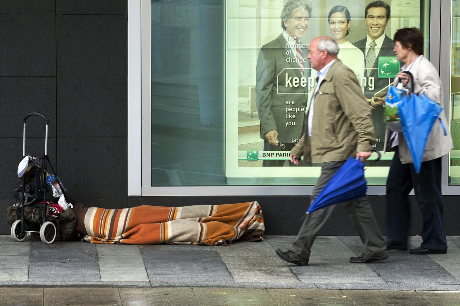 Two persons passe near a homeless which sleeps warp in a carpet on the sidewalk, in Geneva, Switzerland, Saturday, June 29, 2013. (KEYSTONE/Salvatore Di Nolfi)