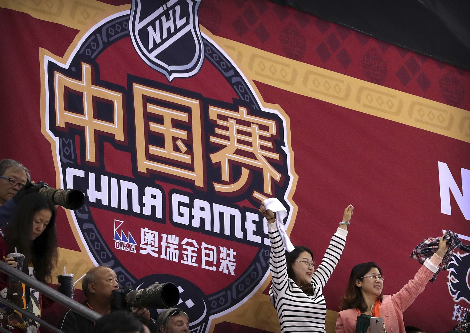 Chinese fans cheer for a Calgary Flames goal during the 2018 NHL China Games hockey game between the Boston Bruins and the Calgary Flames in Beijing, China, Wednesday, Sept. 19, 2018. Boston beat Calgary, 3-1. (AP Photo/Mark Schiefelbein)