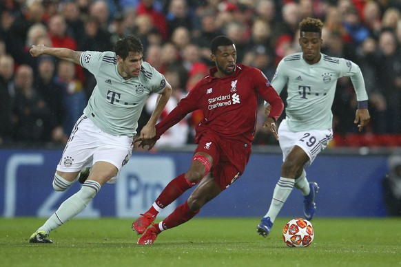 Liverpool's Georginio Wijnaldum, center, competes for the ball with Bayern midfielder Javi Martinez, left, and Bayern forward Kingsley Coman during the Champions League round of 16 first leg soccer match between Liverpool and Bayern Munich at Anfield stadium in Liverpool, England, Tuesday, Feb. 19, 2019. (AP Photo/Dave Thompson)