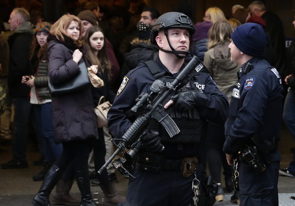 epa05084139 A member of the New York City Police department's Hercules team patrols in Times Square the day before New Year's Eve in New York, NY, USA, 30 December 2015. Thousands of people every year attend the 'Ball Drop' party in the city's famous square when an illuminated globe slides down a pole on the roof of the One Time Square building in the last minute of the old year, illuminating the New Year's number at midnight.  EPA/JASON SZENES