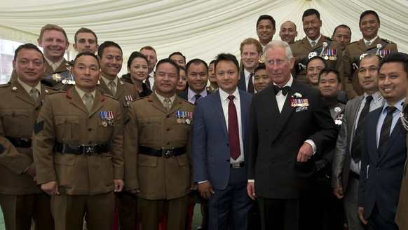 Britain's Prince Charles and Prince Harry, center, poses with a group of Gurkhas at a reception prior to a pageant to celebrate 200 years of Gurkha service to the British Crown in London, Tuesday, June 9, 2015. (AP Photo/Alastair Grant, Pool)
