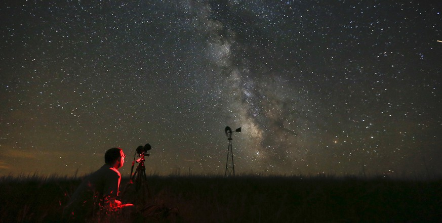 AP10ThingsToSee - Omaha photographer Lane Hickenbottom photographs the night sky in a pasture near Callaway, Neb., Wednesday, July 23, 2014. The Milky Way was visible to the naked eye. (AP Photo/The Wichita Eagle, Travis Heying)