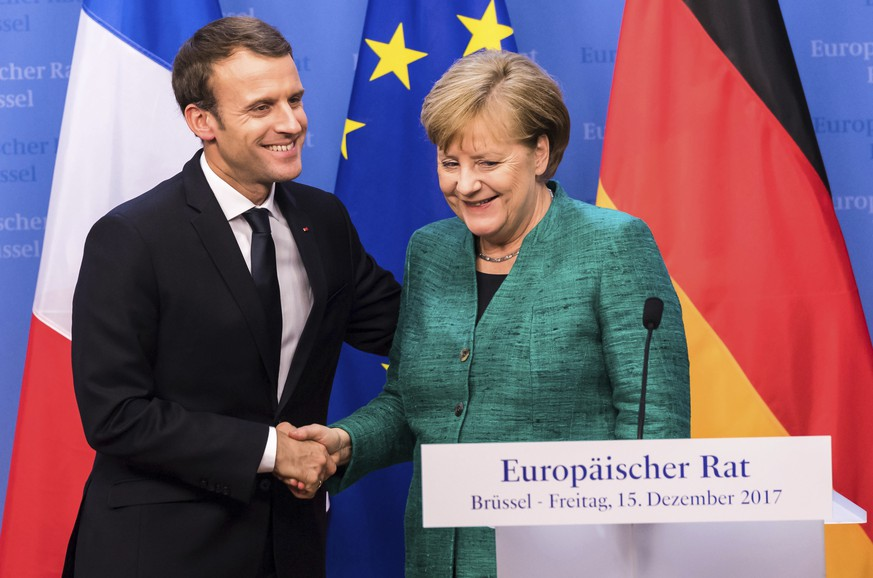 German Chancellor Angela Merkel, right, reaches out to shake hands with French President Emmanuel Macron after addressing a media conference at an EU summit in Brussels on Friday, Dec. 15, 2017. European Union leaders were set Friday to authorize a new phase in Brexit talks as time runs short to clinch an agreement on future relations and trade with Britain before it leaves the bloc in March 2019. (AP Photo/Geert Vanden Wijngaert)