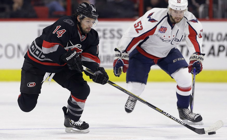 Carolina Hurricanes' Nathan Gerbe (14) controls the puck as Washington Capitals' Mike Green (52) chases during the second period of an NHL hockey game in Raleigh, N.C., Friday, Feb. 27, 2015. Carolina won 3-0. (AP Photo/Gerry Broome)