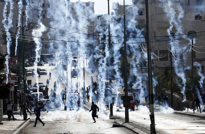 epa05074285 An Israeli borderpolice vehicle shoots tear gas at Palestinians during clashes on the outskirts of the West Bank city of Bethlehem, 18 December 2015.  EPA/ABED AL HASHLAMOUN