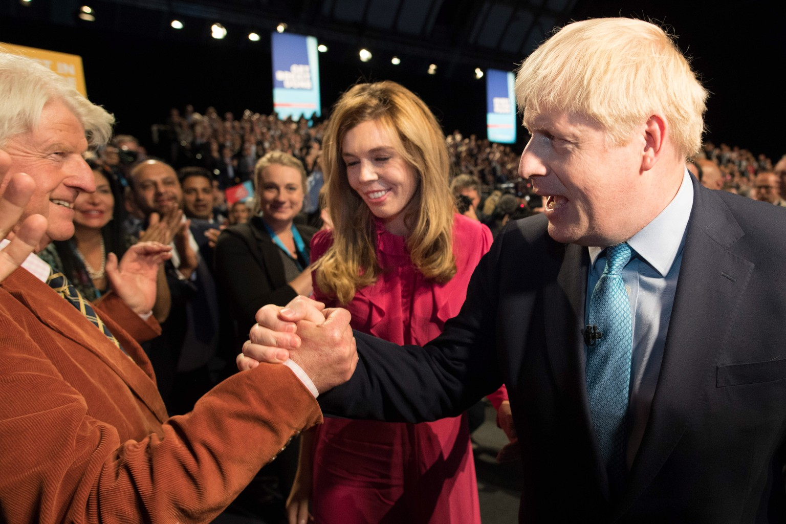epa07889366 Prime Minister Boris Johnson leaves the stage with his partner Carrie Symonds as he is congratulated by his father Stanley Johnson after delivering his speech during the Conservative Party Conference at the Manchester Convention Centre, Britain, 02 October 2019.  EPA/STEFAN ROUSSEAU / POOL