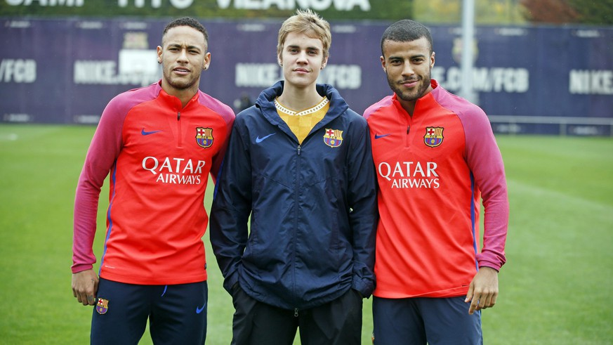 epa05642266 A handout image released by FC Barcelona and made available on 22 November 2016 shows US singer Justin Bieber (C) posing with Brazilian forward Neymar jr. (L) and midfielder Rafinha Alcantara during a training session of FC Barcelona held on 21 November 2016, in Barcelona, northeastern Spain. Bieber is in Spain to give two concerts, tonight in Barcelona and in Madrid on 23 November, as part of his Purpose World Tour.  EPA/MIGUEL RUIZ ONLY EDITORIAL USE, NO SALES  EDITORIAL USE ONLY/NO SALES