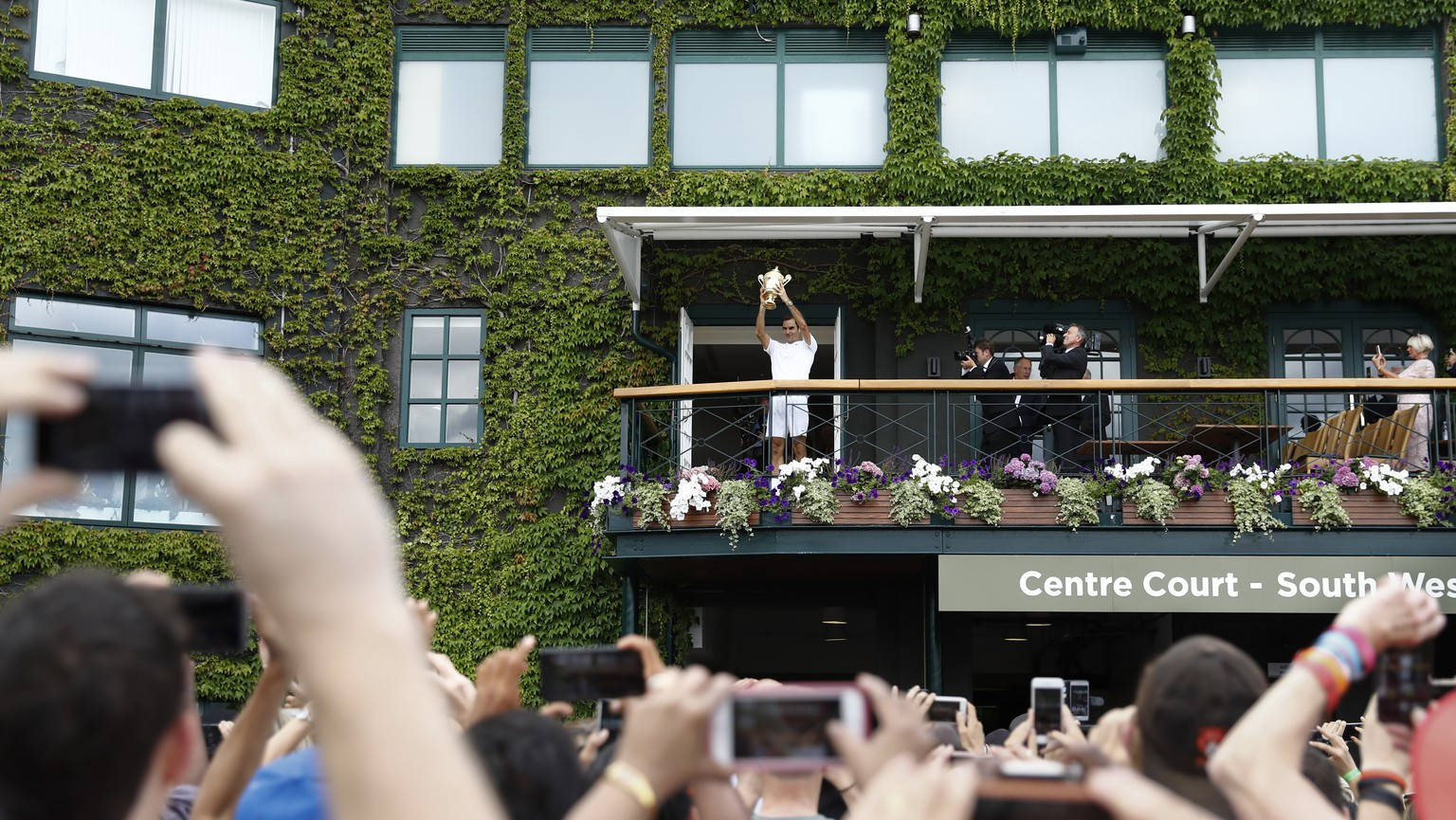 Roger Federer of Switzerland celebrates with the trophy on the balcony of the centre court after winning the men's final match against Marin Cilic of Croatia during the Wimbledon Championships at the All England Lawn Tennis Club, in London, Britain, 16 July 2017. (KEYSTONE/Peter Klaunzer)