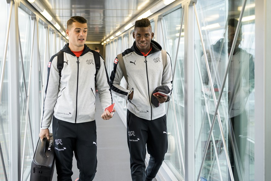 Switzerland's soccer players Granit Xhaka, left, and Breel Embolo, right, react before taking the aircraft at the EuroAirport Basel Mulhouse, in Basel, Switzerland, Sunday, October 8, 2017. Switzerland soccer team will face Portugal soccer team for the 2018 Fifa World Cup group B qualifying soccer match on Tuesday, October 10, in Lisbon. (KEYSTONE/Jean-Christophe Bott)