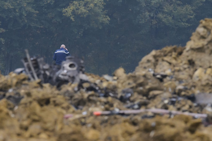 A French Gendarmerie officer walks next to the crash scene with pieces of a wreckage of a Swiss Army F/A-18 jet, in Glamondans, near Besancon, in France, Wednesday, 14 October 2015. An F/A-18 jet fighter belonging to the Swiss Air Force crashed on Wednesday morning during a training exercise in eastern France. The one-seater aircraft crashed into an uninhabited area. The pilot, who ejected to safety, has been injured. (KEYSTONE/Jean-Christophe Bott)