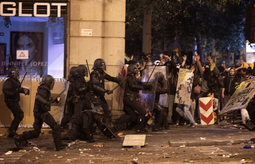National police officers clash with demonstrator during clashes in Barcelona, Spain, Friday, Oct. 18, 2019.The Catalan regional capital is bracing for a fifth day of protests over the conviction of a dozen Catalan independence leaders. Five marches of tens of thousands from inland towns are converging in Barcelona's center for a mass protest. (AP Photo/Emilio Morenatti)