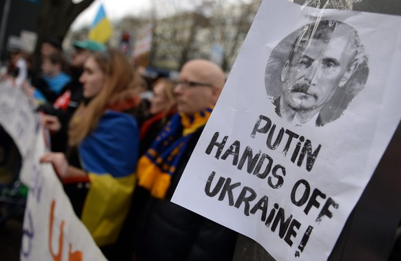 epa04106128 A placard depicting joined faces of Stalin and Putin and reading 'Putin Hands off Ukraine' is seen during a demonstration in front of the Russian embassy in Berlin, Germany, 02 March 2014. More than 200 people gathered for the protest against a possible  EPA/BRITTA PEDERSEN