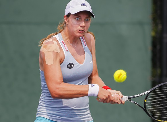 epa04676333 Stefanie Voegele of Switzerland returns the ball to Shahar Peer of Israel during their qualifying round match of the Miami Open tennis tournament at the Crandon Park Tennis Center on Key Biscayne in Miami, Florida, USA, 23 March 2015.  EPA/ERIK S. LESSER
