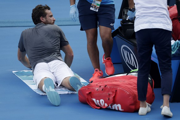 Latvia's Ernests Gulbis waits to receive treatment during his first round match against Switzerland's Stan Wawrinka at the Australian Open tennis championships in Melbourne, Australia, Tuesday, Jan. 15, 2019. (AP Photo/Kin Cheung)