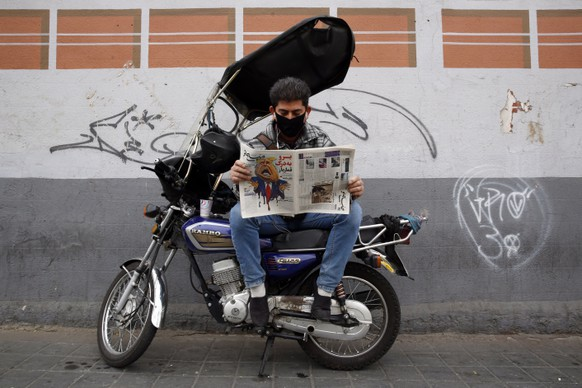 epa08803965 A man reads a copy of Iranian daily newspaper Sobhe Nou with a cartoon depicting US president Donald J Trump and a headline reading 'Go to hell gambler', in front of a newsstand in Tehran, Iran, 07 November 2020. According to local media reports, many Iranians are rooting for Democratic candidate Joe Biden.  EPA/ABEDIN TAHERKENAREH
