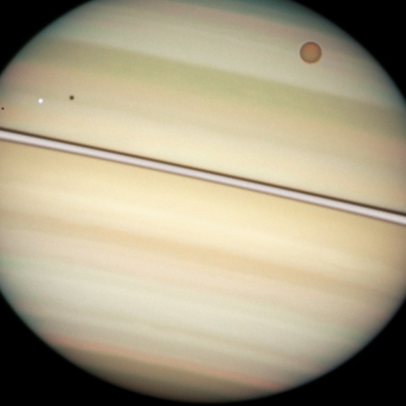 This close-up view of Saturn's disc captures the transit of several moons across the face of the gas giant planet. The giant orange moon Titan - larger than the planet Mercury - can be seen at upper right. The white icy moons that are much closer to Saturn, hence much closer to the ring plane in this view, are, from left to right: Enceladus, Dione, and Mimas. The dark band running across the face of the planet slightly above the rings is the shadow of the rings cast on the planet. This picture was taken with Hubble's Wide Field Planetary Camera 2 on 24 February 2009, when Saturn was at a distance of roughly 1.25 billion kilometres from Earth. Hubble can see details as small as 300 kilometres across on Saturn.