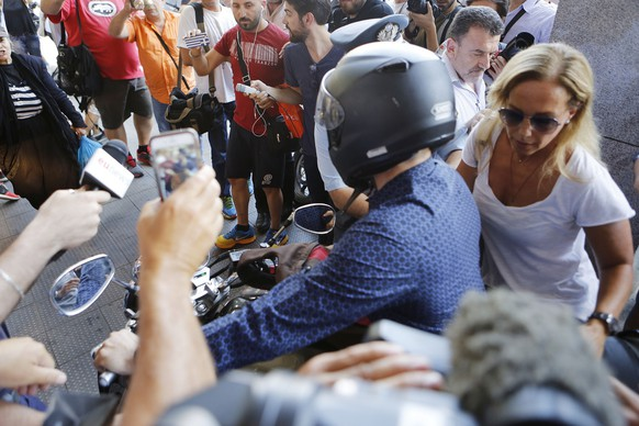 Outgoing Greek Finance Minister Yanis Varoufakis, left, and his wife Danae Stratou leave on a motorcycle after his resignation in Athens, Monday, July 6, 2015. Greece and its membership in Europe's joint currency faced an uncertain future Monday, with the country under pressure to reach a bailout deal with creditors as soon as possible after Greeks resoundingly rejected the notion of more austerity in exchange for aid. (AP Photo/Petros Karadjias)