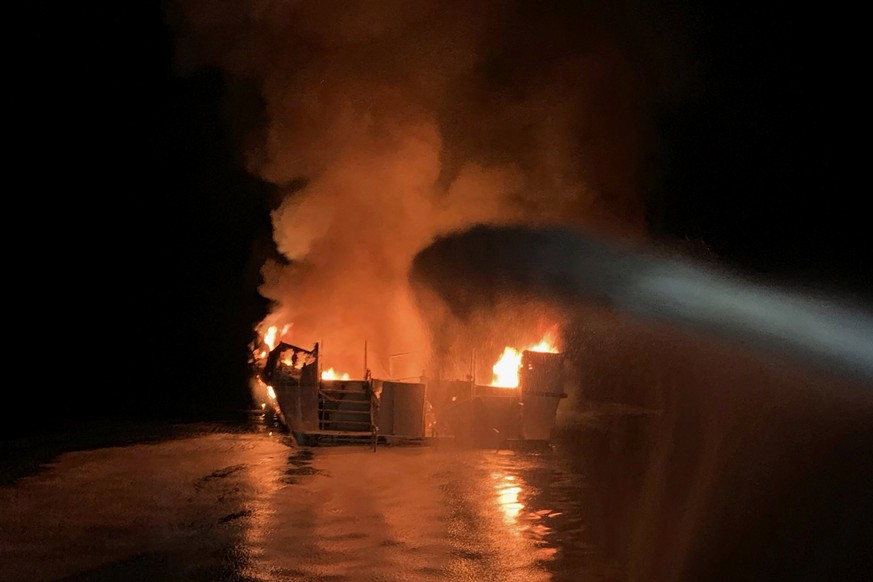 In this photo provided by the Ventura County Fire Department, VCFD firefighters respond to a boat fire off the coast of southern California, Monday, Sept. 2, 2019. The U.S. Coast Guard said it has launched several boats to help over two dozen people