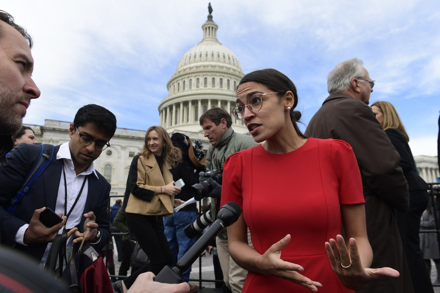 FILE - In this Nov. 14, 2018, file photo, Rep.-elect Alexandria Ocasio-Cortez, D-N.Y., talks with reporters following a photo opportunity on Capitol Hill in Washington, with the freshman class. Ocasio-Cortez seems to be everywhere. She's cooked soup, live on Instagram. She's done laundry in public. And she's clapped back at critics of her clothing and a misstatement. The New York Democrat, who at 29 is the youngest woman to be elected to Congress, says she's documenting her journey to Capitol Hill to lift some of the mystery of the place and make it, 'real.'  (AP Photo/Susan Walsh, File)