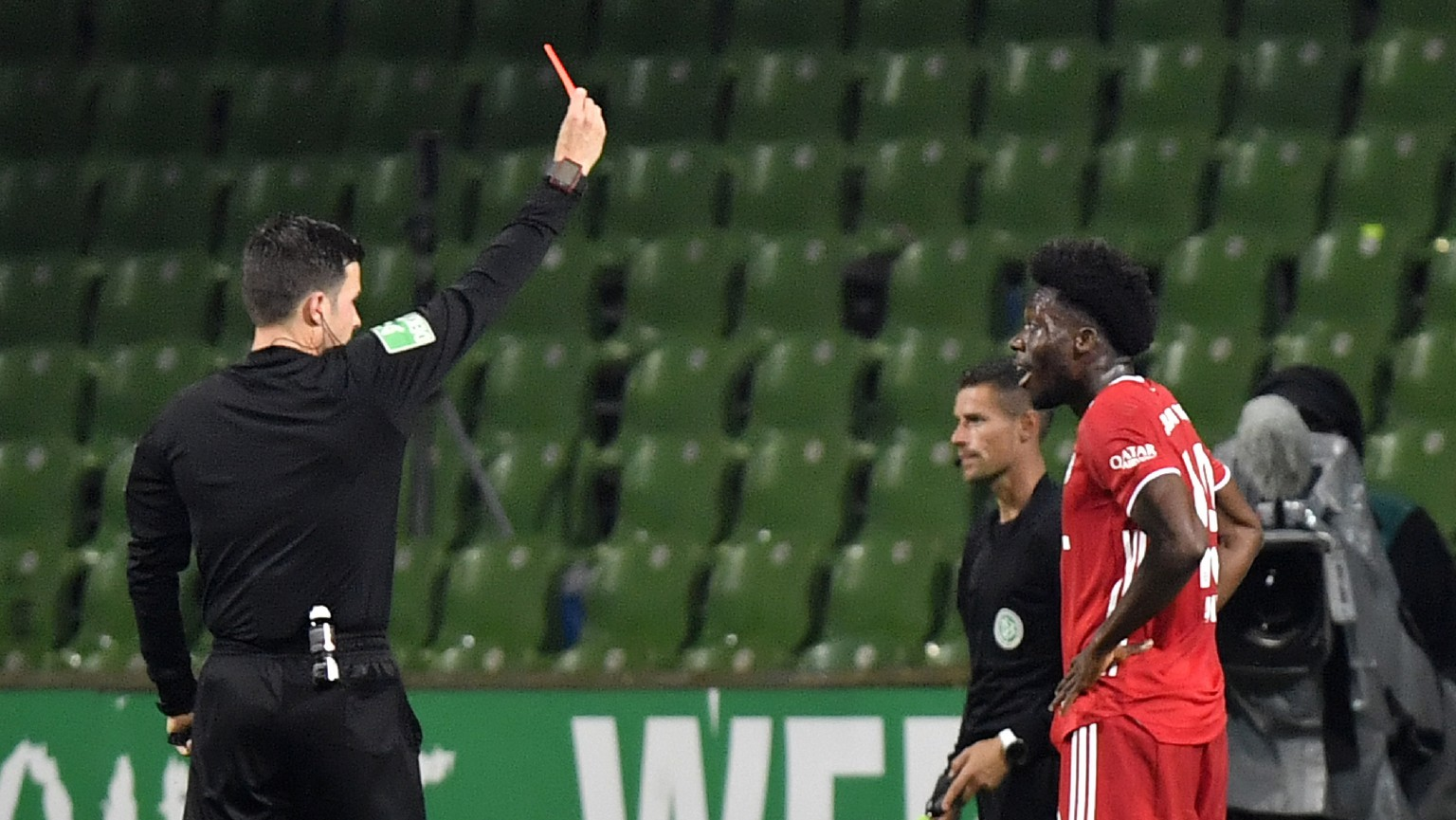 Referee Harm Osmers shows the red card to Bayern's Alphonso Davies during the German Bundesliga soccer match between Werder Bremen and Bayern Munich in Bremen, Germany, Tuesday, June 16, 2020. Because of the coronavirus outbreak all soccer matches of the German Bundesliga take place without spectators. (AP Photo/Martin Meissner, Pool)