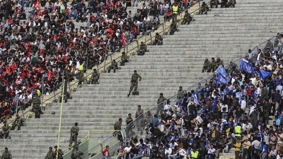 Iranian police officers, center, take position between supporters of soccer teams, Esteghlal, right, and Persepolis, left, in their derby match, during Iran's premier league, at the Azadi (Freedom) stadium in Tehran, Iran, Wednesday, March 30, 2011. In a tight security for Iran's top two soccer teams derby and in front of some 70,000 spectators Esteghlal defeated Persepolis 1-0. (AP Photo/Vahid Salemi)