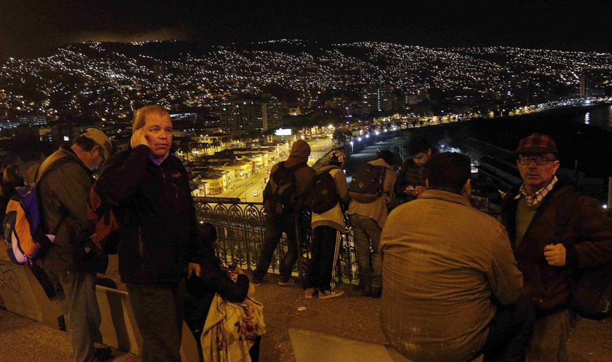 epa04934245 A group of people who left their houses in Valparaiso, Chile, late 16 September 2015, after a tsunami alert was issued for the earthquake of 8.3 on the Richter scale. A strong earthquake of magnitude 8.3 rattled Chilean capital Santiago and other regions of the country the US Geological Service reported. There were no immediate reports of casualties, and coastal areas around Chile were being evacuated for fear of a tsunami. First waves have reached the shore.  EPA/RAUL ZAMORA