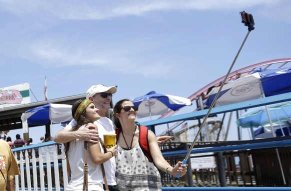 Visitors to Coney Island use a selfie stick to take a photo with the Wonder Wheel in the background, Friday, July 3, 2015, in the Brooklyn borough of New York. Temperatures will be in the mid 70s and 80s for the 4th of July holiday weekend. (AP Photo/Mary Altaffer)
