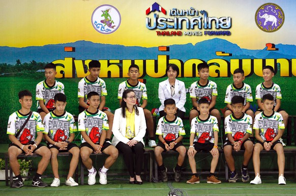 epa06896386 The 12 rescued members of the Wild Boar soccer team, with their assistant coach Ekapol Chantawong (front, L), make their first public appearance with child psychologists during a military governmental TV pool broadcasting program at Chiang Rai Provincial Administrative Organization in Chiang Rai province, Thailand, 18 July 2018. The thirteen members of Wild Boar child soccer team, including their assistant coach, who were trapped in the Tham Luang cave since 23 June 2018, made their first appearance on the day for a tightly-controlled interview with the media after they were rescued, before returning to their homes with families.  EPA/PONGMANAT TASIRI